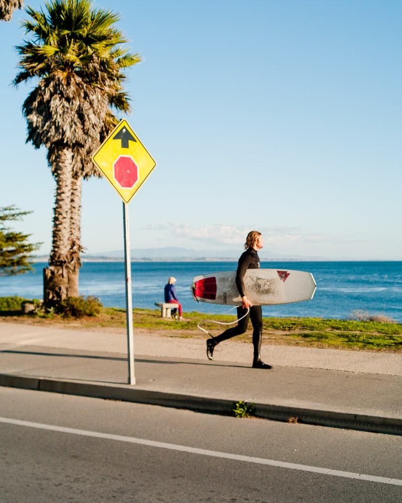 man in beach with surfboard